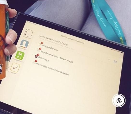 Ein Tablet liegt auf dem Schoß einer Person. Das Tablet zeigt ein Programm mit verschiedenen Optionen.
