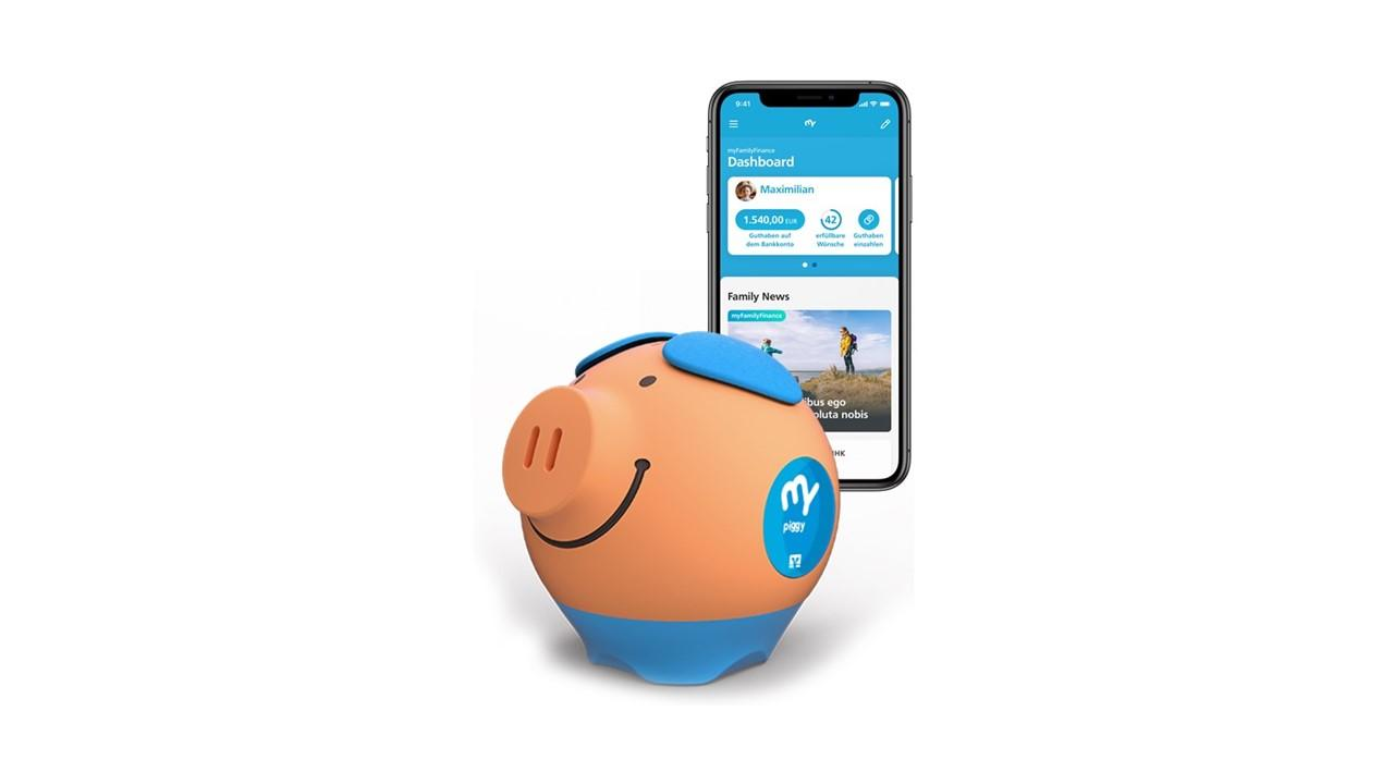 Ein Sparschwein steht vor einem Smartphone. Das Smartphone zeigt eine Banking-App.