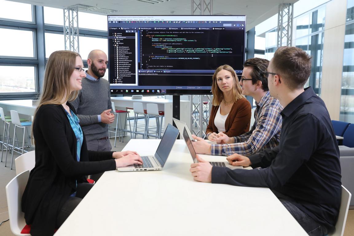 Das Bild zeigt Studierende in einem Konferenzraum.