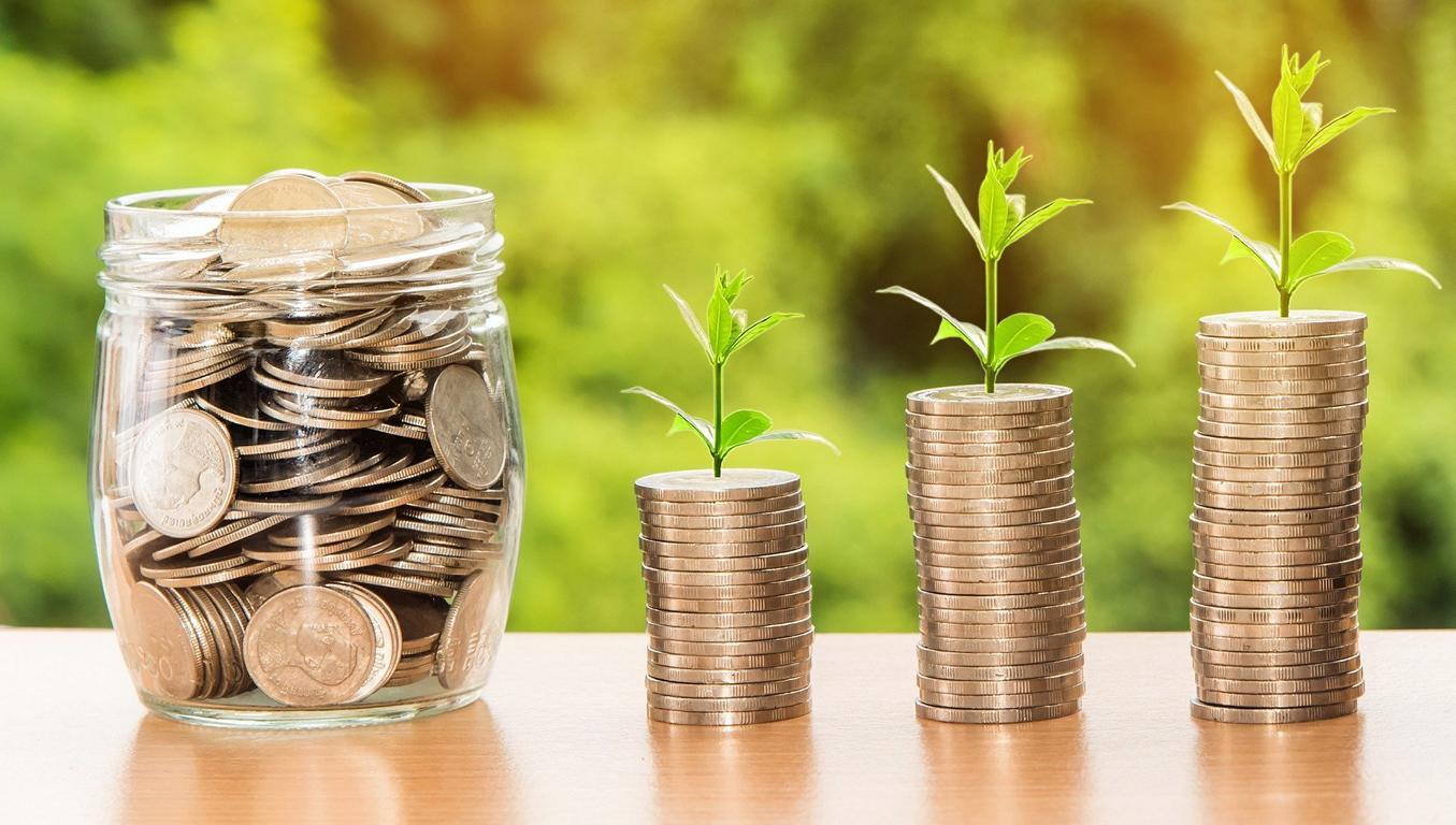 Münzen in einem Glas, daneben Münzstapel, aus denen eine Pflanze wächst.