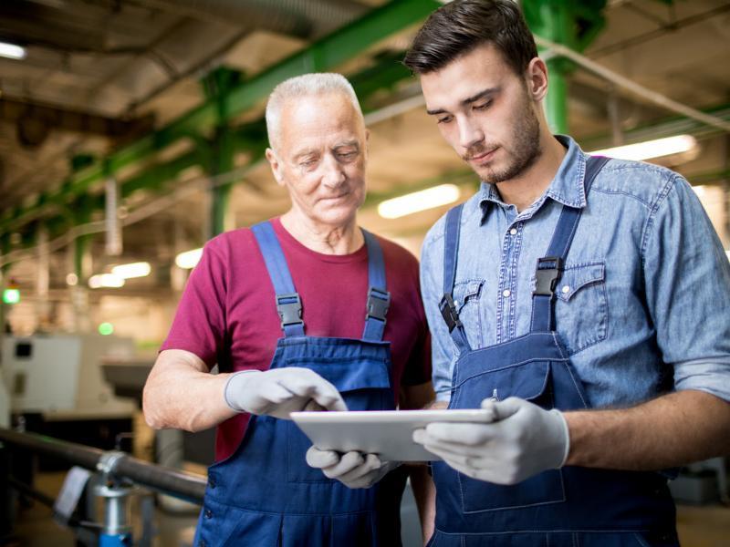 Zwei Männer in Arbeitskleidung mit einem Tablet