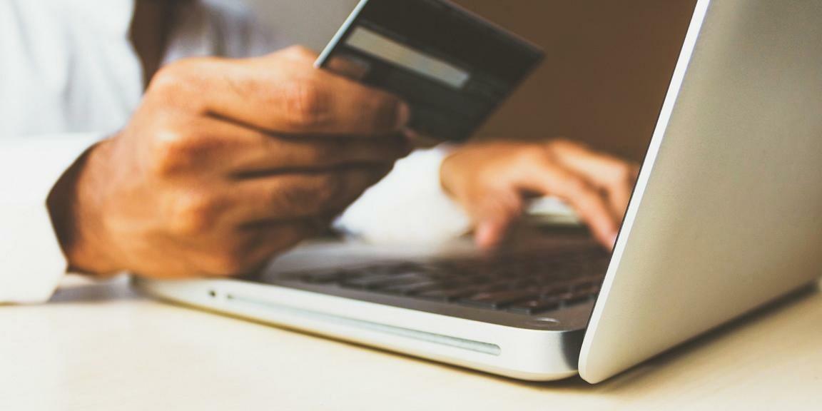 Person mit Kreditkarte sitzt vor Laptop.