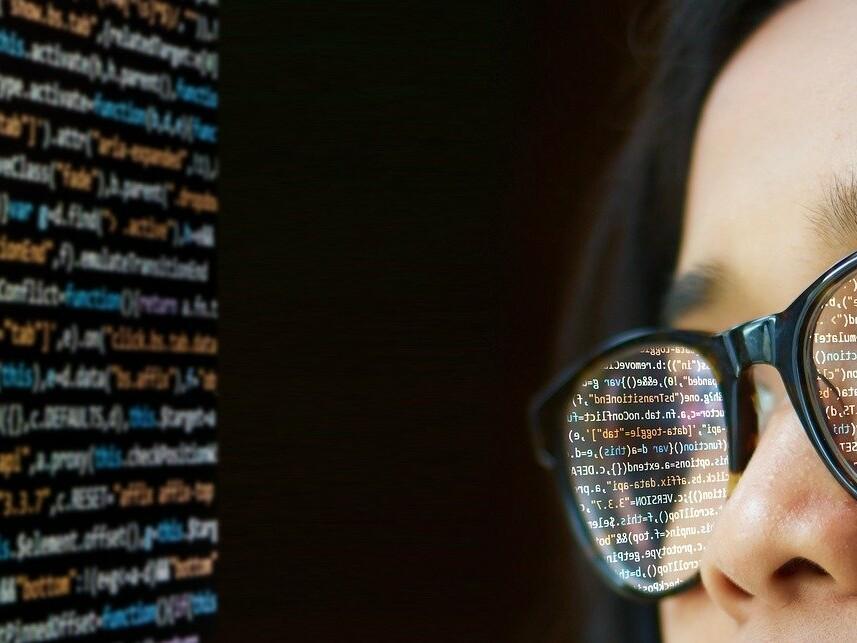 Frau blickt auf Programmiercode, der sich in ihrer Brille spiegelt.