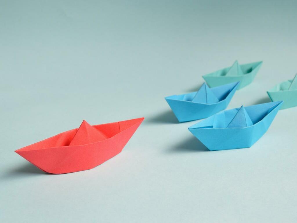 Papierboote folgen einem Papierboot an der Spitze.
