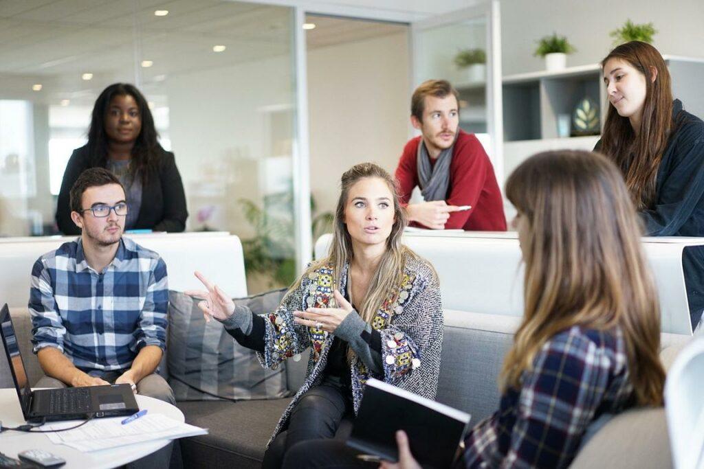 Teamwork: Mehrere Mitarbeitenden sitzen zusammen und unterhalten sich.