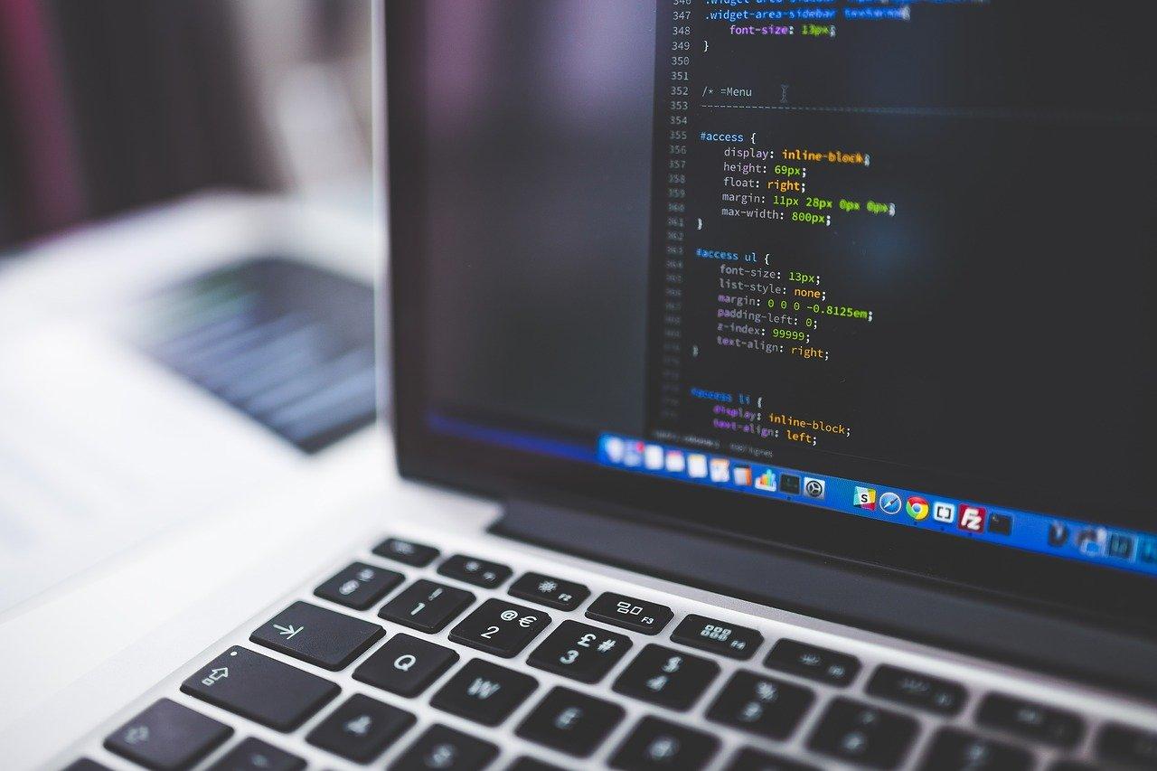Aufgeklappter Laptop mit Programmierzeilen auf dem Bildschirm.