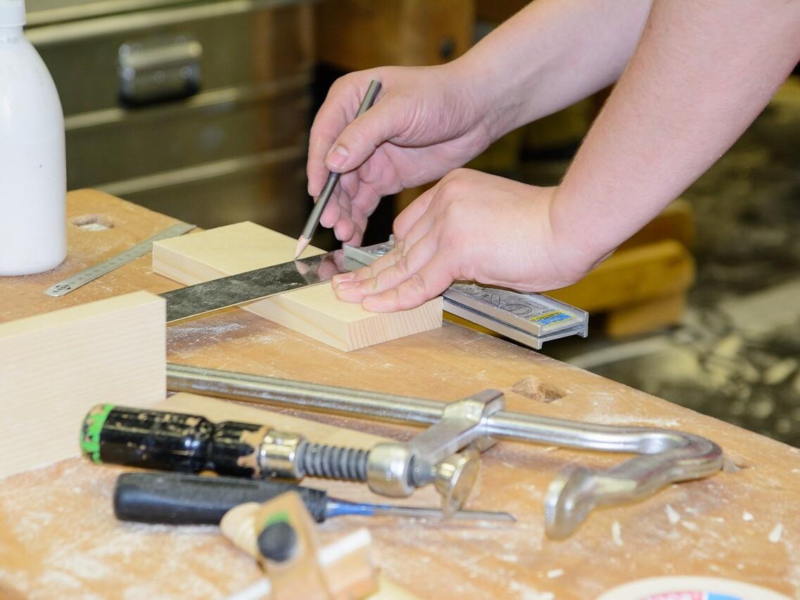 Handwerker an einer Werkbank beim Anzeichnen und Vermessen eines Werkstücks aus Holz.