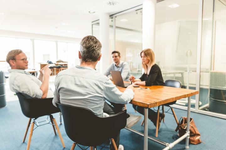 Konferenzraum mit einer Frau und drei Männern am Tisch.