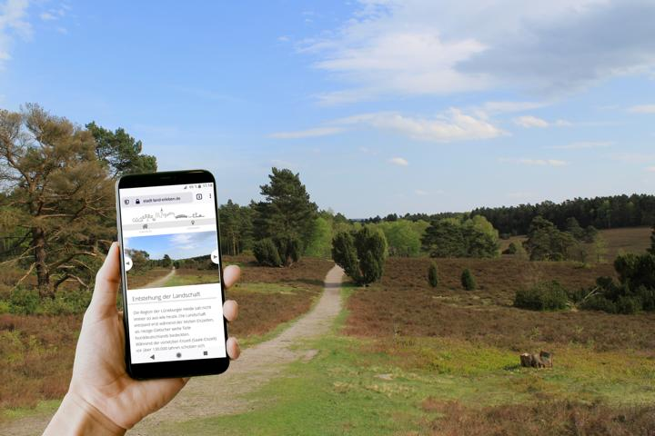 Fotomontage aus Heidelandschaft und Hand mit Smartphone.